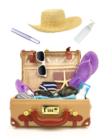 Ready to travel open suitcase with summer equipment isolated