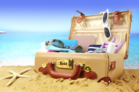 travel luggage: Full open suitcase on tropical beach background