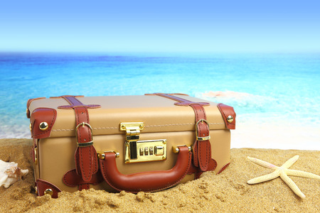agencia de viajes: Maleta cerrado en el fondo de playa Foto de archivo