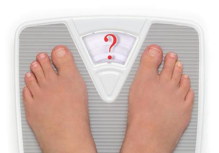 health questions: Female feet on bathroom scale with question mark symbol