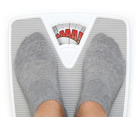 overeat: Female feet on funny bathroom scale