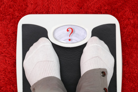 eating questions: Female feet on bathroom scale with question mark symbol