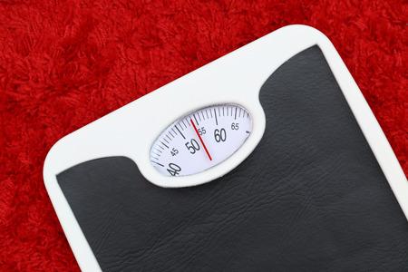 low calories: Bathroom scale on red bath mat