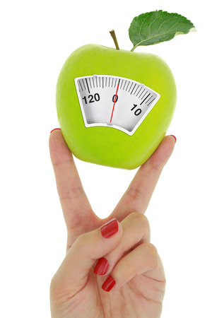nutritionist: Hand and fresh green apple with weight scale dial