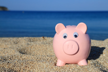 Summer piggy bank on the beach photo