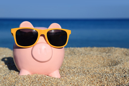 Summer piggy bank with sunglasses on the beach Stock fotó