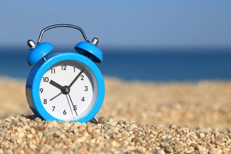 Vacation time. Alarm clock on the beach photo
