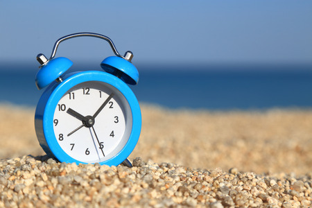 Vacation time. Alarm clock on the beach photo