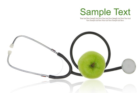 Stethoscope with green apple isolated on white  photo