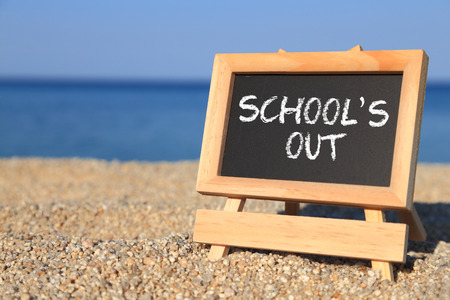 Blackboard with Schools out text on the beach