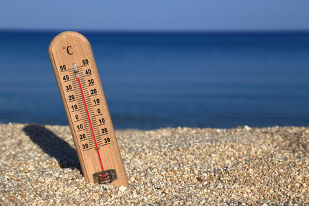 Thermometer on a beach shows high temperatures photo