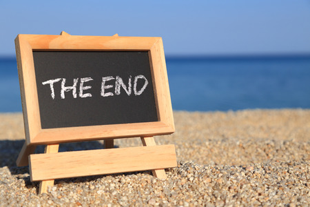 returns: Blackboard with The end text on the beach