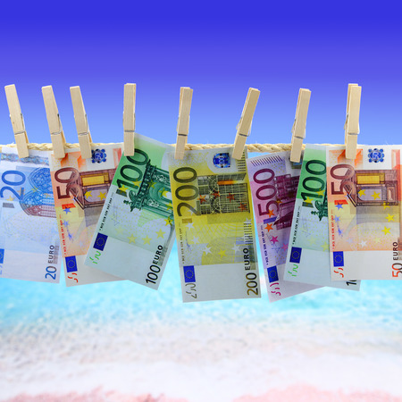 Banknotes hanging on clothesline in front of the beach photo