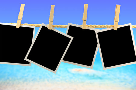 Photo frames hanging on a rope in front of the sea photo