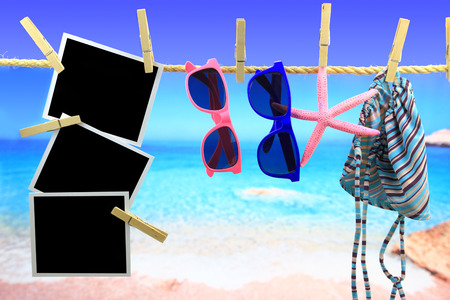 Photo frames and beach items hanging on a rope in front of the sea photo