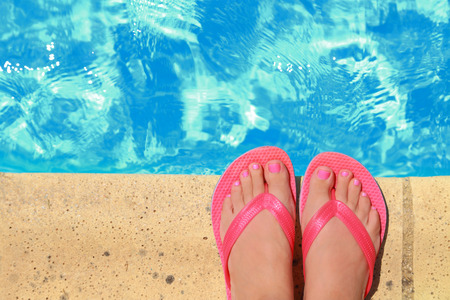 Female feet with flip flops by the pool photo