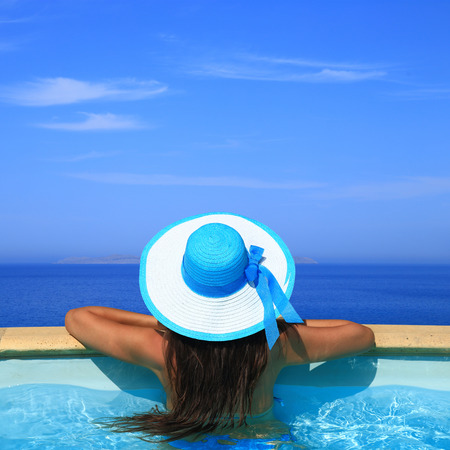 luxury lifestyle: Woman overlooking the sea from swimming pool  Stock Photo