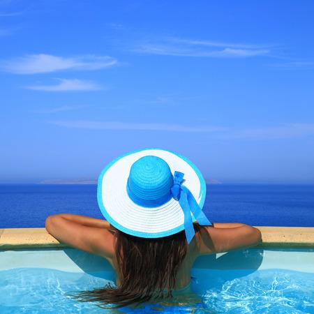 santorini: Woman overlooking the sea from swimming pool  Stock Photo