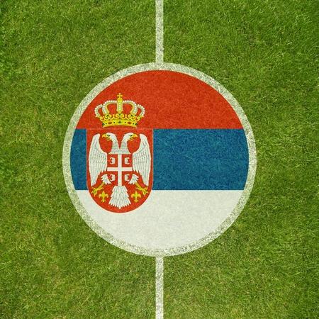 serbian: Football field center closeup with Serbian flag in circle  Stock Photo
