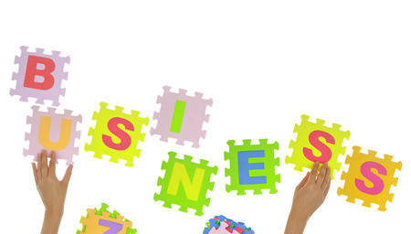 Hands forming word Business with jigsaw puzzle pieces isolated photo