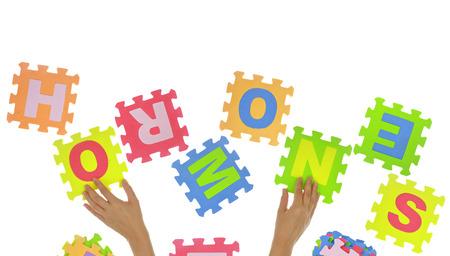 """psicologia infantil: Manos que forman la palabra """"Hormonas"""" con piezas de un rompecabezas aislados Foto de archivo"""