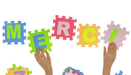 french text: Hands forming word Merci with jigsaw puzzle pieces isolated