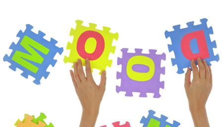 """psicologia infantil: Manos que forman la palabra """"estado de ánimo"""" con piezas de un rompecabezas aislados Foto de archivo"""