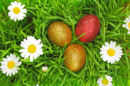 Easter background with grass, flowers and colorful glitter eggs photo