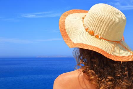 agencia de viajes: Mujer con sombrero con vistas al primer plano del paisaje marino