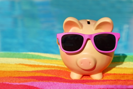 holiday profits: Summer piggy bank with sunglasses in front of a swimming pool