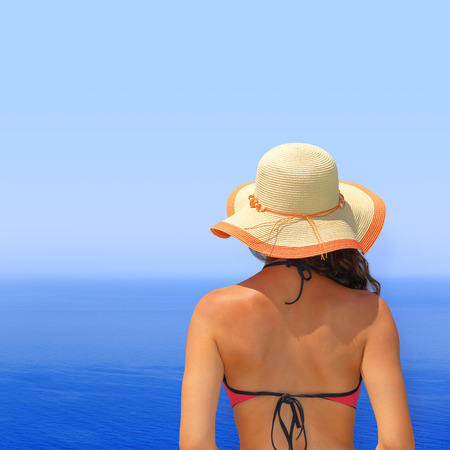 Woman in bikini and hat overlooking the seascape photo