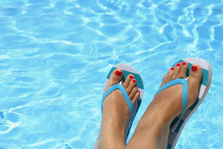 Female wet feet with flip flops by the pool