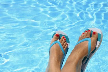 Vrouwelijke natte voeten met slippers bij het zwembad Stockfoto