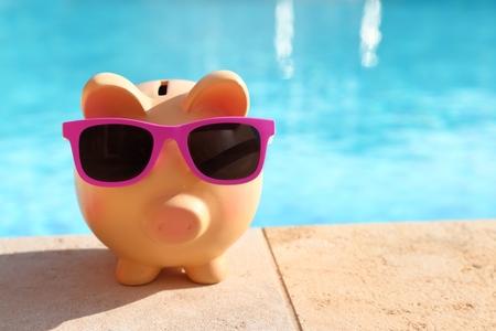 agencia de viajes: Alcancía de verano con gafas de sol en frente de una piscina Foto de archivo