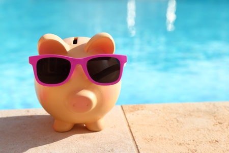 Summer piggy bank with sunglasses in front of a swimming pool
