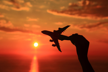 Silhouette of hand holding airplane miniature with sunset background  photo