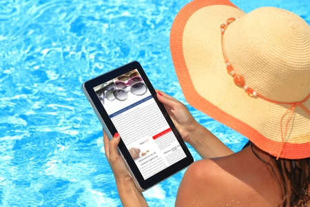 Woman holding tablet computer in the pool photo