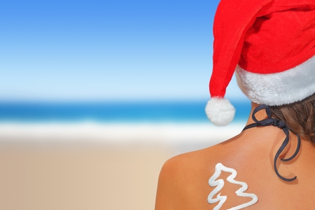 feliz navidad: Woman on the beach in santas hat with Christmas tree shaped sunscreen