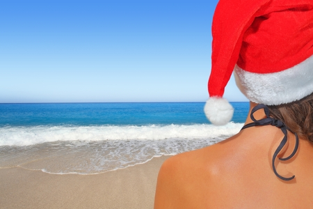 beach happy new year: Woman on the beach in santas hat Stock Photo