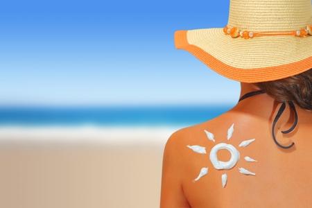 Donna con crema solare a forma di sole sulla schiena
