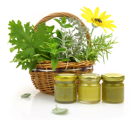 Fresh herbs in wicker basket and cosmetic creams Stock Photo