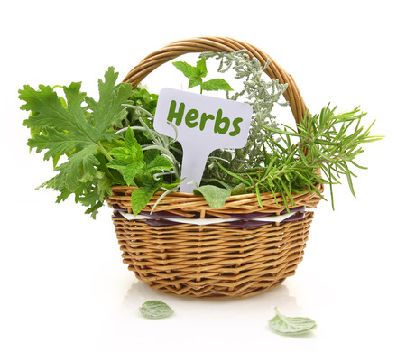 Fresh herbs in wicker basket with a tag