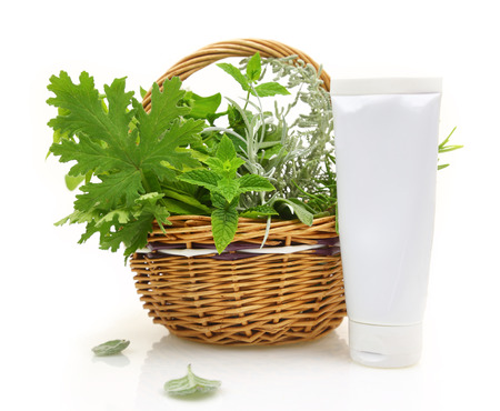 Fresh herbs in wicker basket and cream tube photo