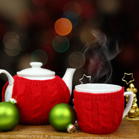 warm drink: Christmas decoration, teapot and cup in front of sparkle lights Stock Photo