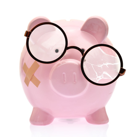 Piggy bank with broken eyeglasses and bandage Stock Photo