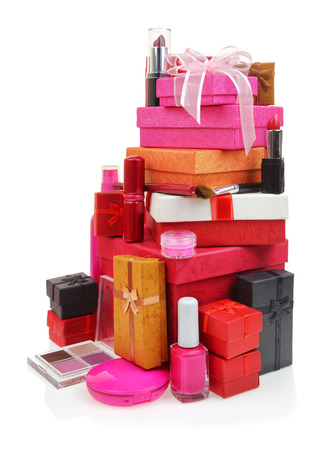 Cosmetics and stack of gift boxes on white background