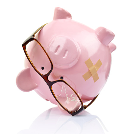 Piggy bank with broken eyeglasses and bandage upside down  photo