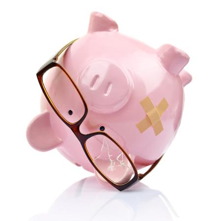 broke: Piggy bank with broken eyeglasses and bandage upside down
