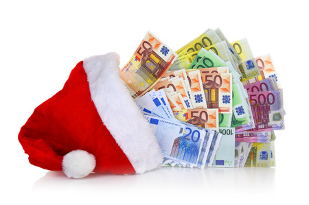 christmas profits: Euro banknotes coming out of Santa Claus hat on white background