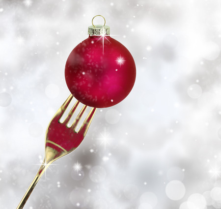 Golden fork with Christmas ball in a glittery background photo